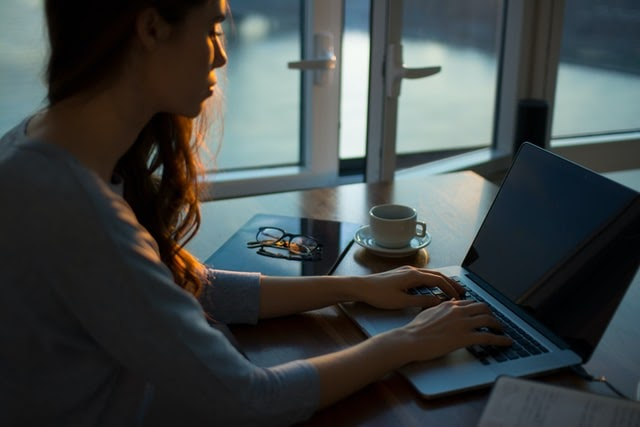 Woman typing on laptop at work