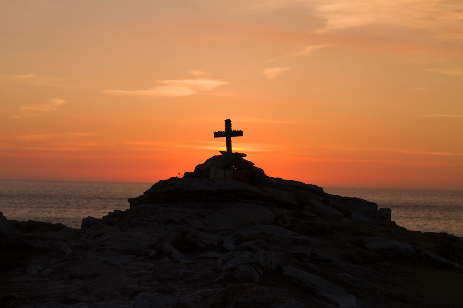 A cross on a cliff over the ocean at sunset
