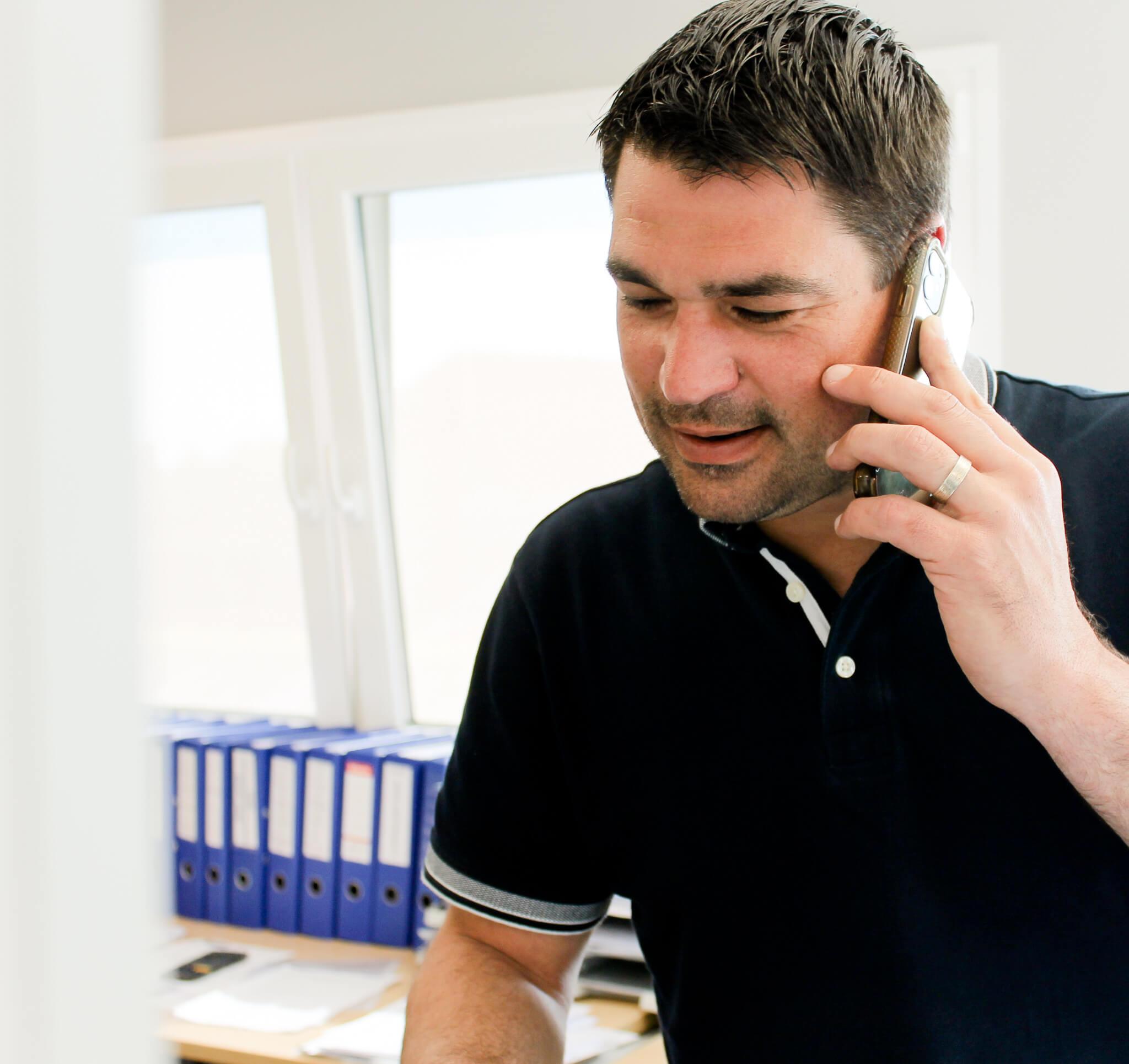 Foto van Christophe aan het telefoneren in kantoor.
