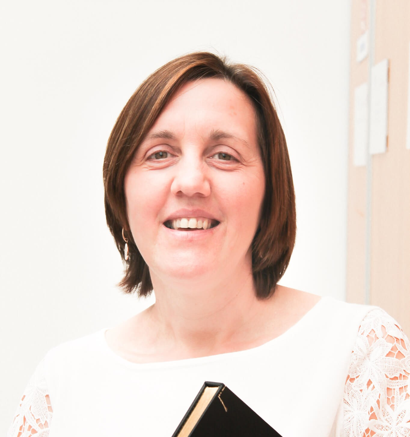 Foto van Hilde in kantoor waarbij ze een boek vasthoudt.
