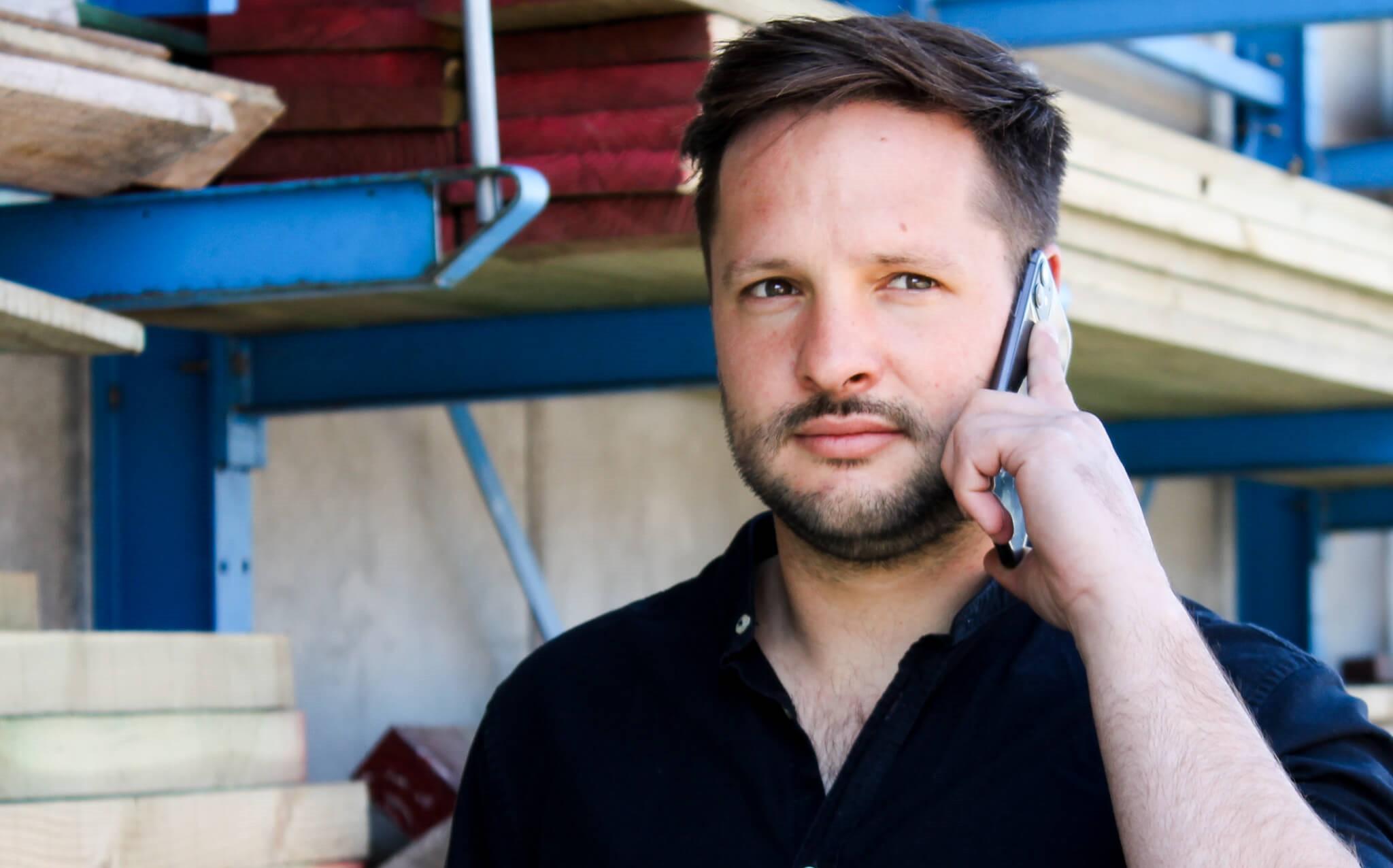 Davy in donker hemd aan het telefoneren.