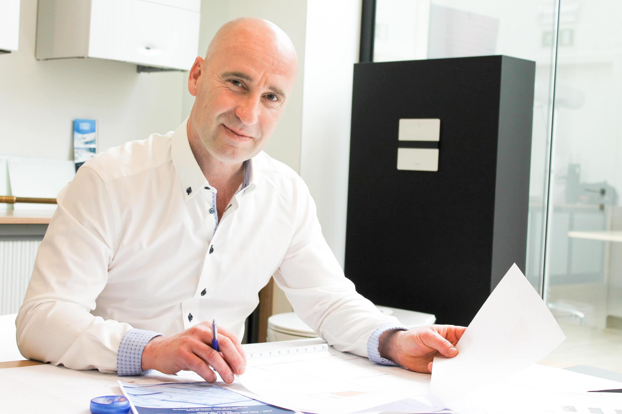 Foto van David in wit hemd, werkend aan bureau. Bewerken van technische tekeningen.