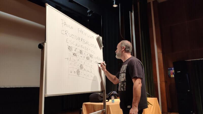 Paulo Freixinho a escrever num quadro numa sessão do clube de palavras cruzadas