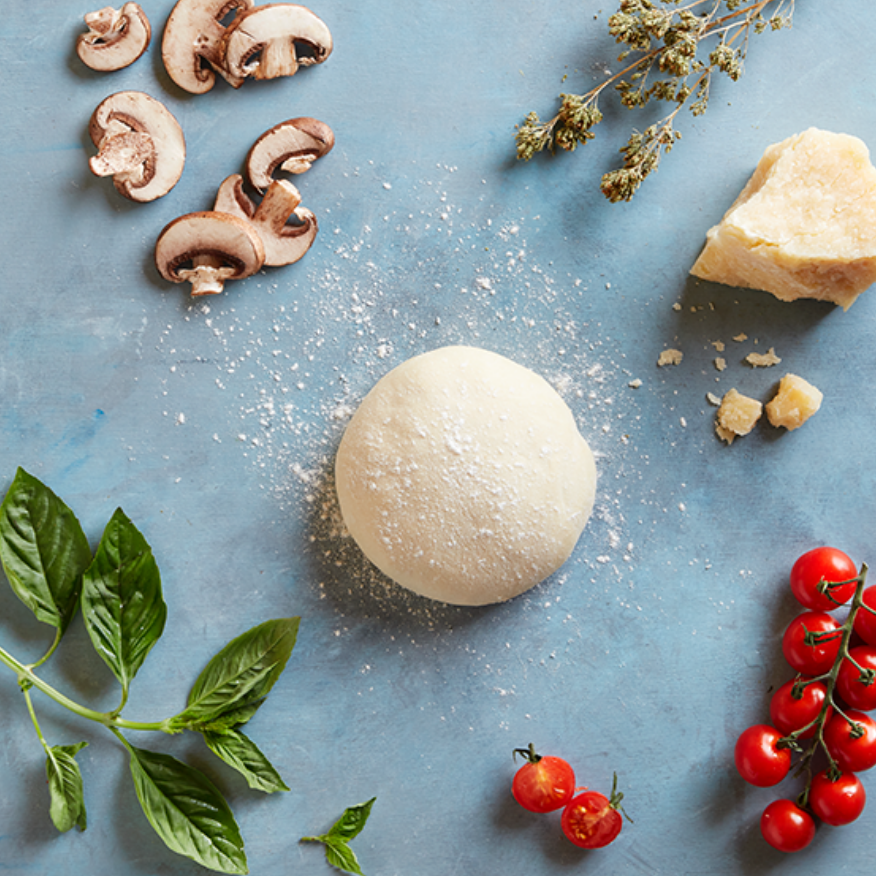 Pizza dough surrounded by beautiful ingredients like tomatoes, mushrooms, wild Italian oregano, and grana pad cheese.