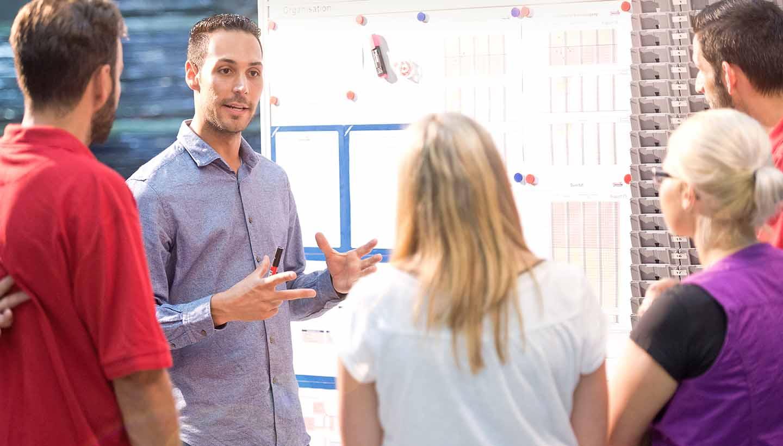 Mitarbeiter Schäflein diskutieren vor einem Flipchart