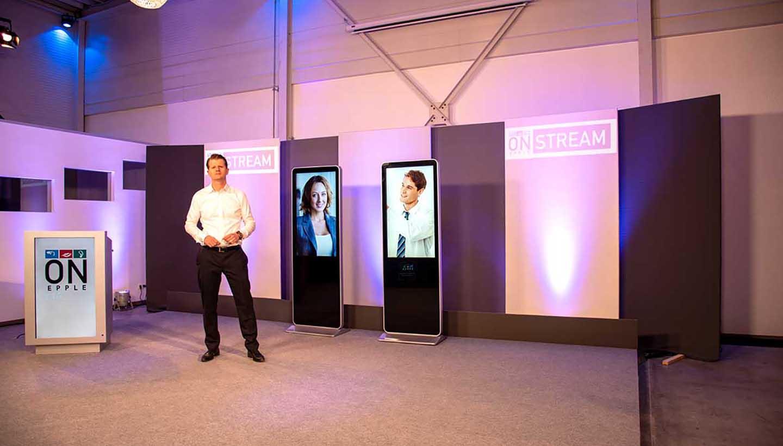 Bühne mit Moderator und Video-Stelen im Veranstaltungsraum von Urban Industrial