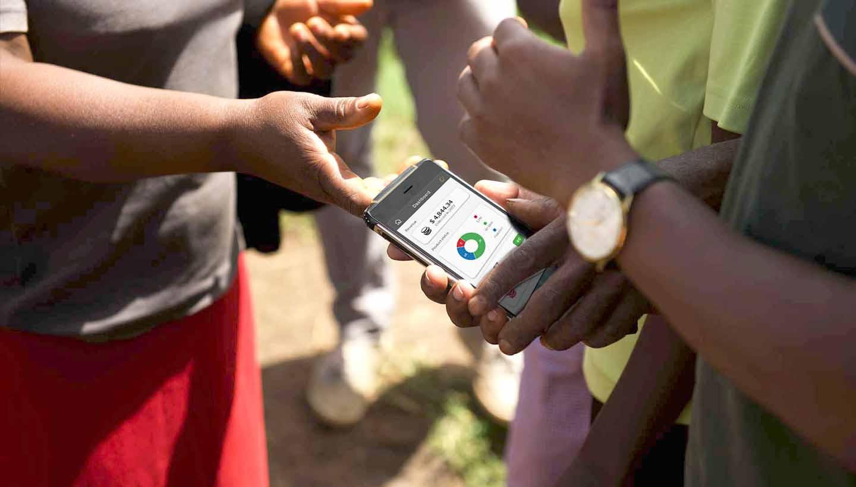 Farbige Menschen halten ein Smartphone mit der geöffneten App von mango solar in in der Hand