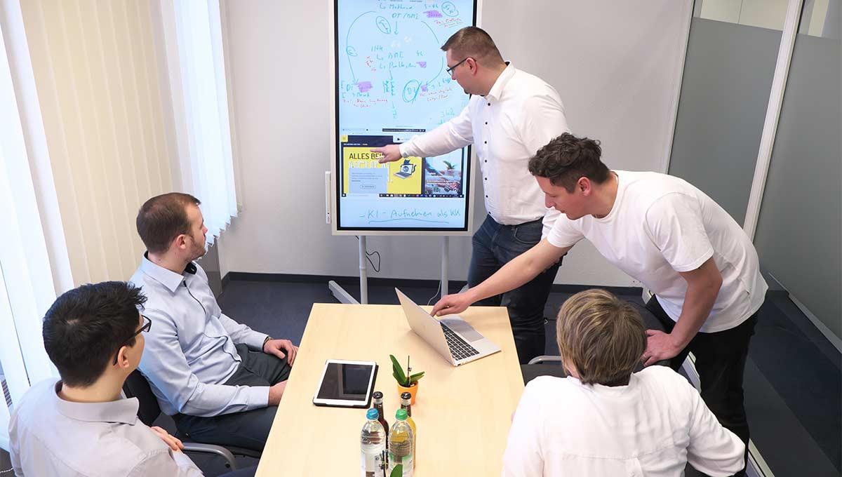 Das fünfköpfige Team des Digitalisierungszentrums bei einer Besprechung im Konferenzraum.