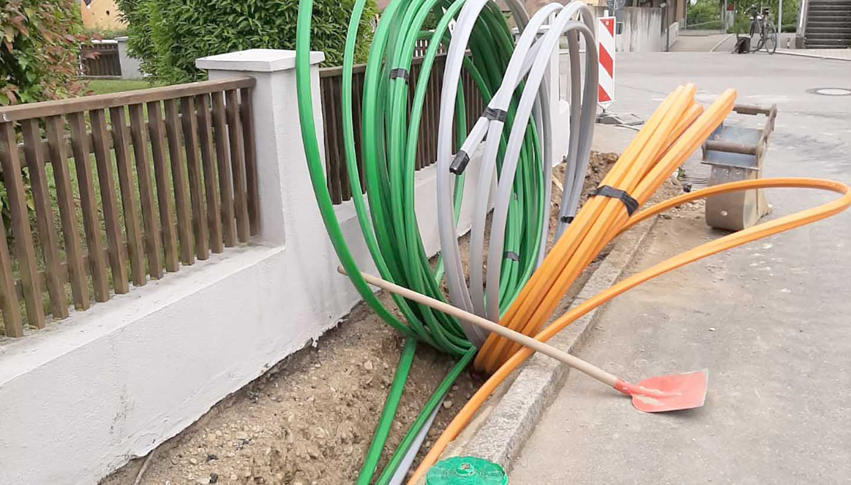 Eine Baustelle: große Kabelrollen mit Leerrohren und Schaufeln