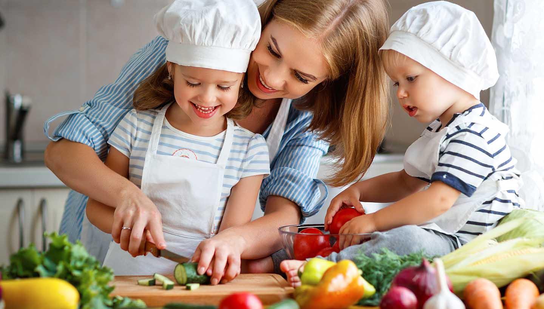 Kinder haben Spaß beim Kochen zusammen mit einer Frau