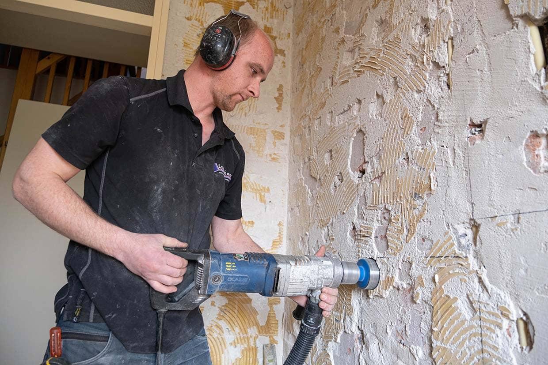 Medewerker Lageschaar boort gat in muur