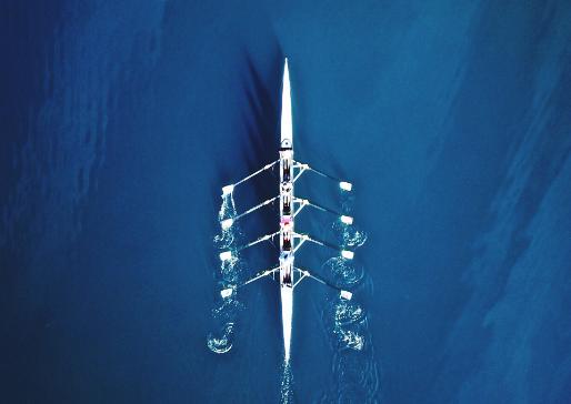 Bovenaanzicht roeiers in blauw water