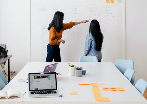 Twee vrouwen staan met hun rug naar een vergadertafel met post-its en laptop terwijl ze wijzen naar whiteboard