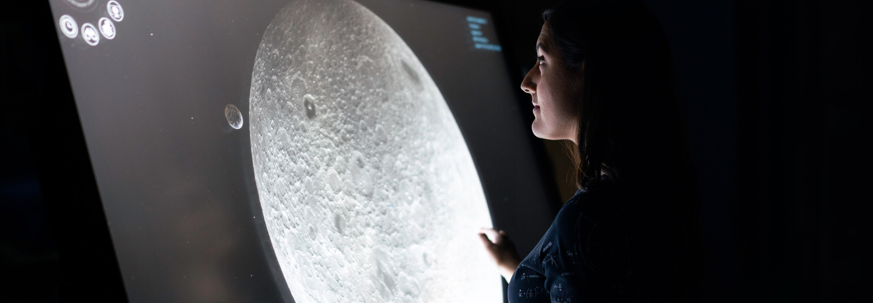 Woman looking at a screen showing information about Earth's moon