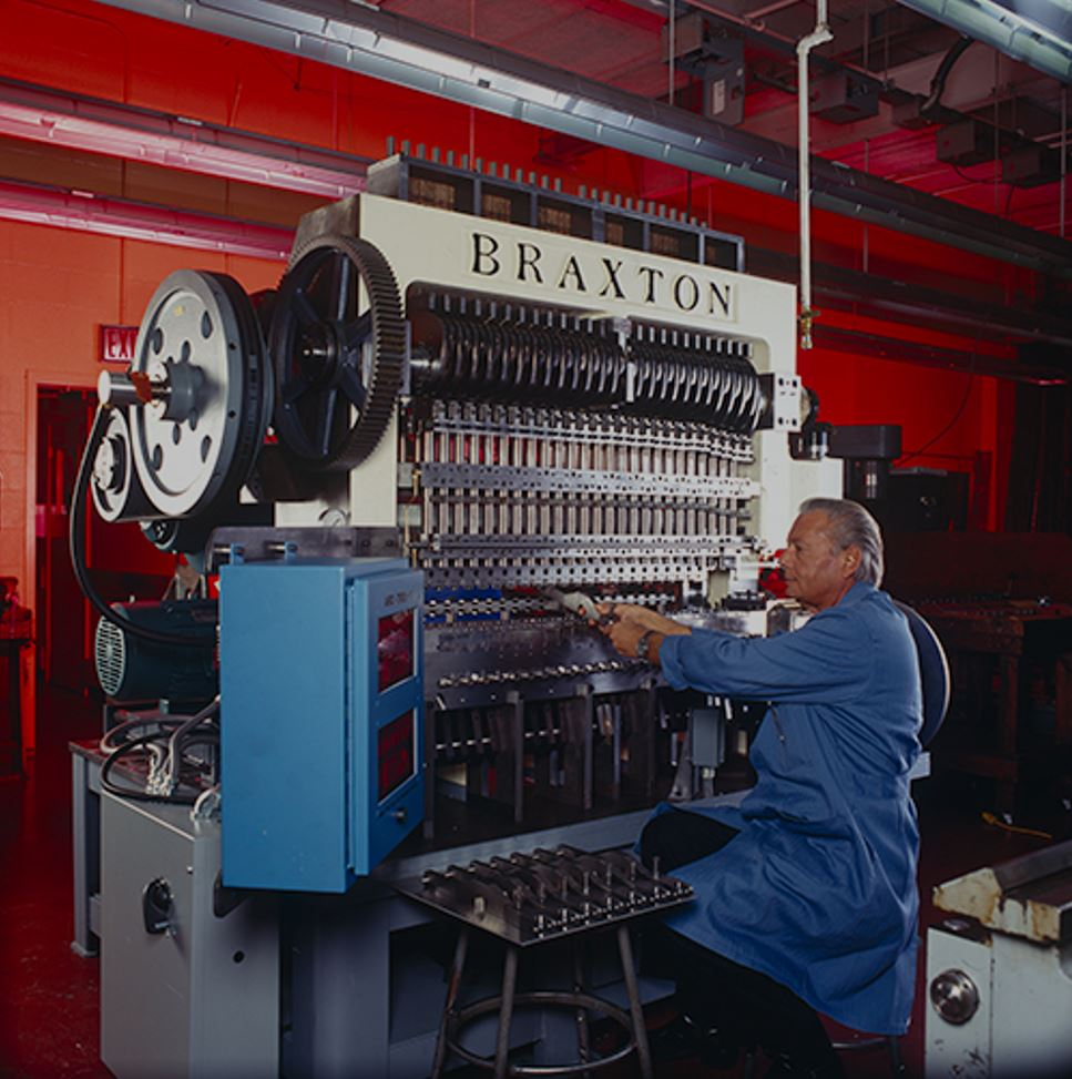 Braxton Nelson in front of eyelet machine.