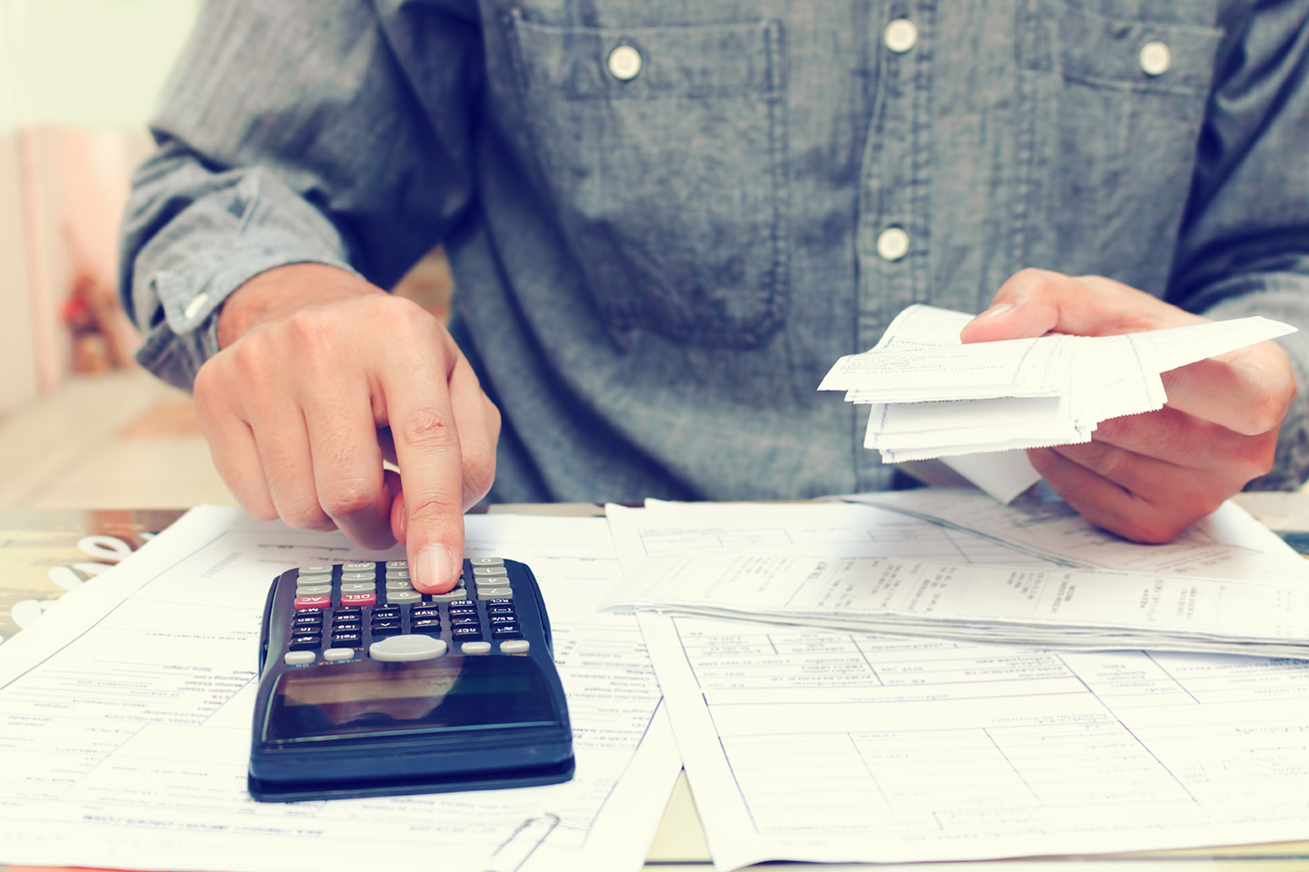 VAT registration and reporting explained, image of a man working out tax on a calculator | Crunch