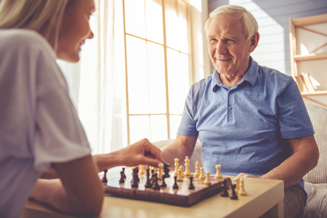 Care Workers - what are your rights at work? Image of woman playing chess with an elderly man | Crunch