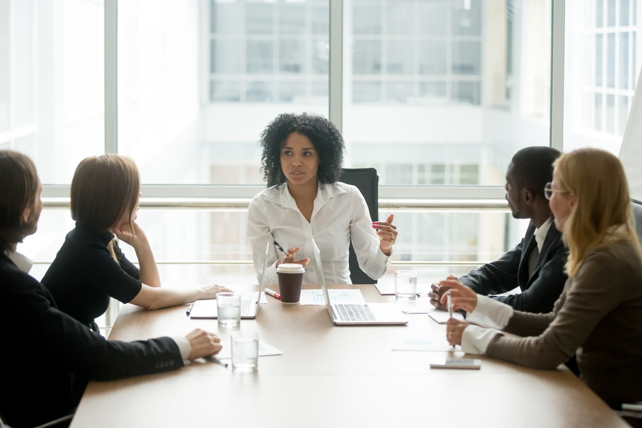 Gender, ethnicity, and executive pay gaps and gender pay gap reporting. Image of a woman leading a corporate meeting | Crunch