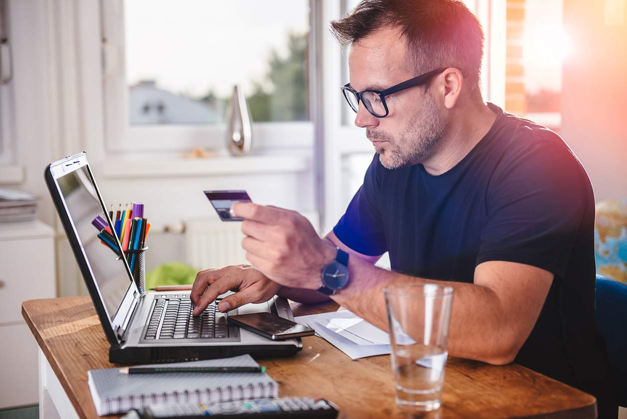 How to pay yourself as a sole trader and how much to put aside for tax, image of a man at a laptop | Crunch