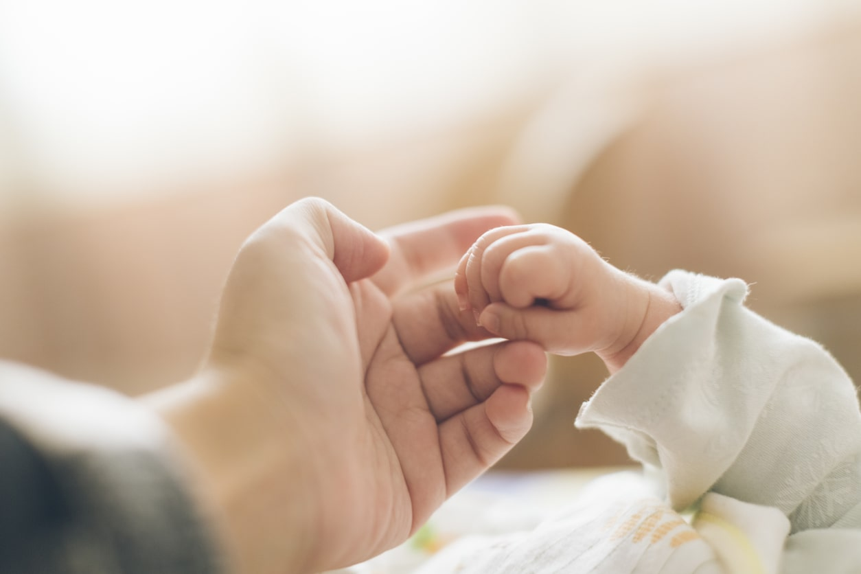 Guide To Maternity Leave and Pay. Image of woman holding baby's hand | Crunch