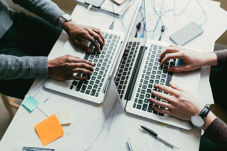 Overhead hands on laptops