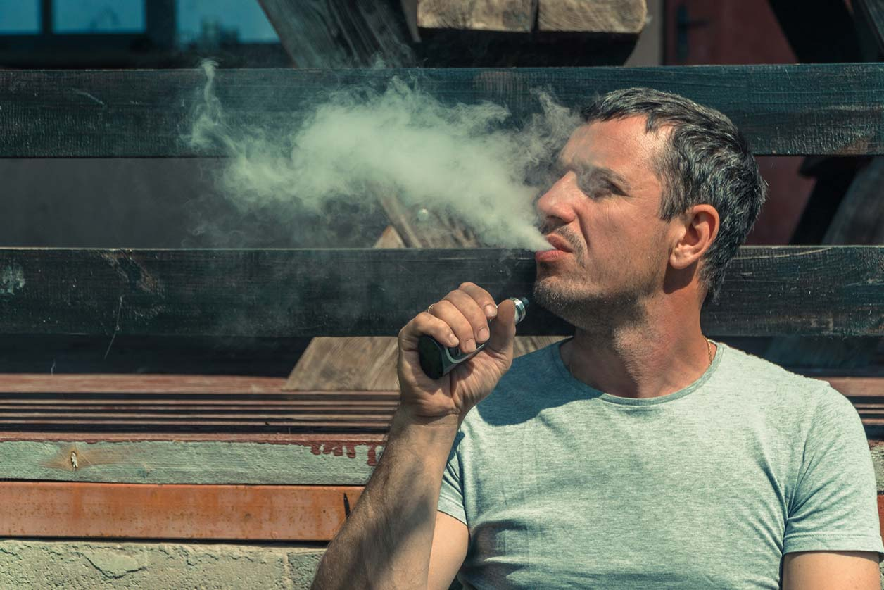 Should you let staff and freelancers smoke e-cigarettes at work?, image of someone smoking an e-cigarette | Crunch
