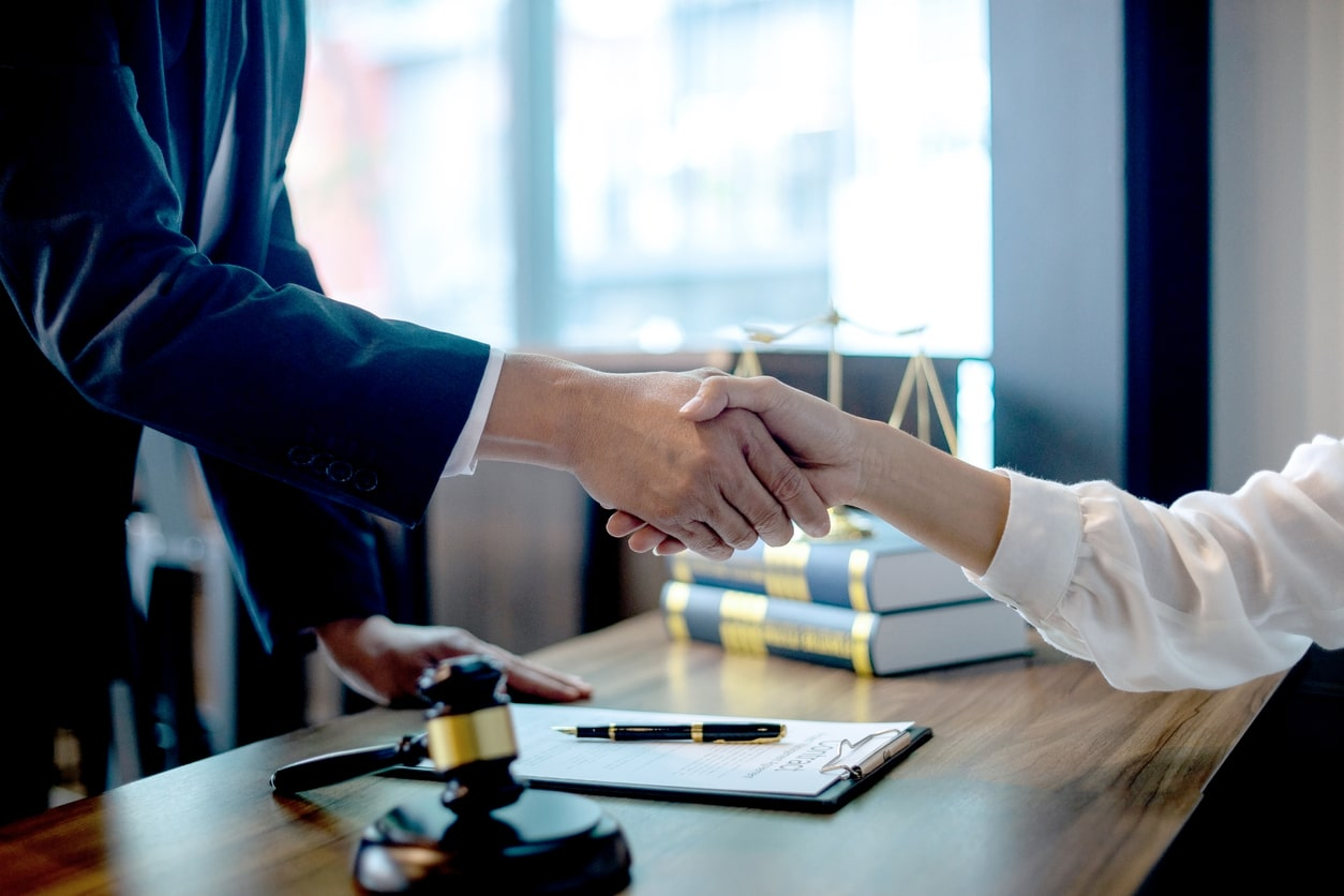 How to deal with an ACAS conciliation request. Image of someone shaking hands with a judge