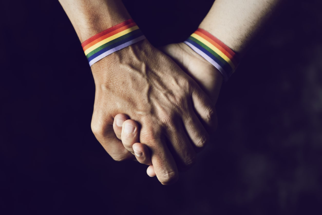Limited company contractors not always protected under Equality Act. Image of people holding hands with rainbow wrist bands