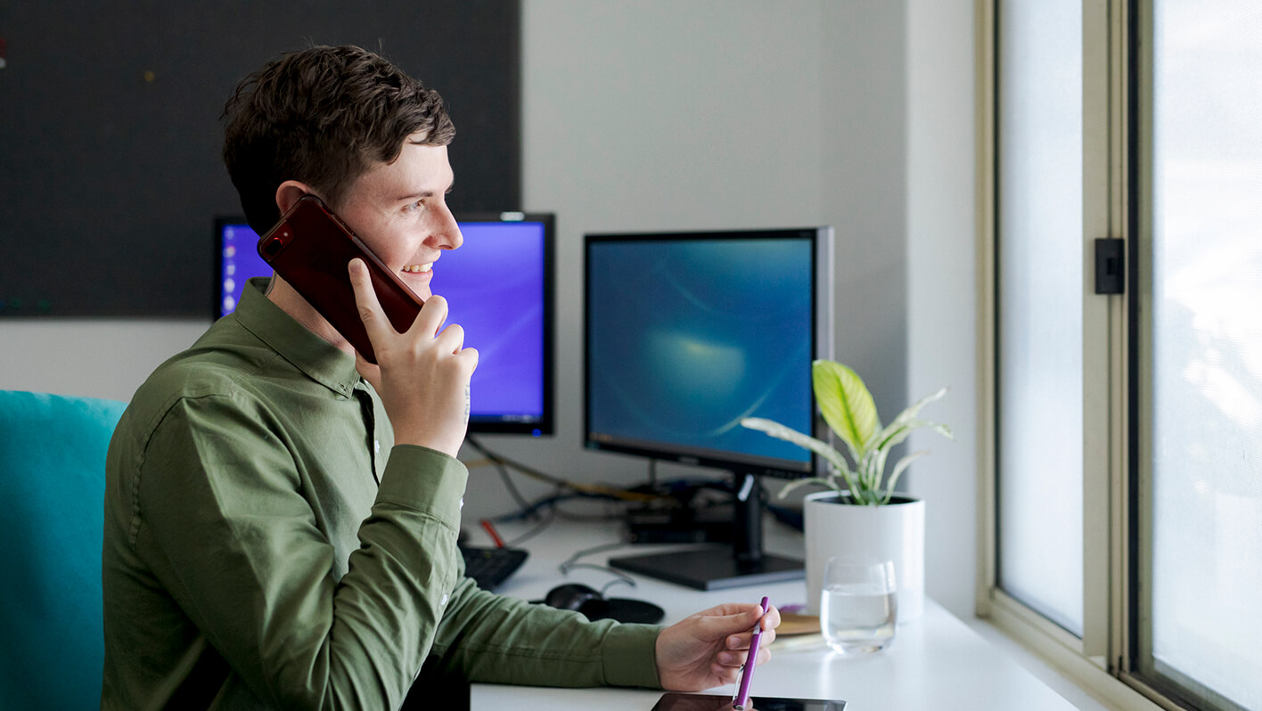 Man in green shirt sits at a desk looking out the window. He holds his mobile phone to his ear with his right hand and holds a pen with his left hand..