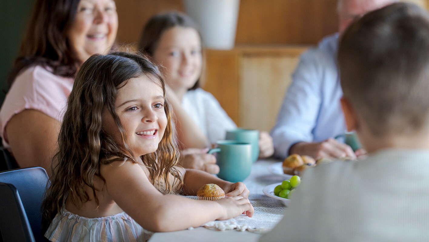 A family sits around a table containing mugs, grapes and a plate of muffins. A young girl is in focus and smiling. Behind her, but out of focus we can see grandmother, sister and grandfather. They are all looking over at someone whose head is blurred in the foreground.