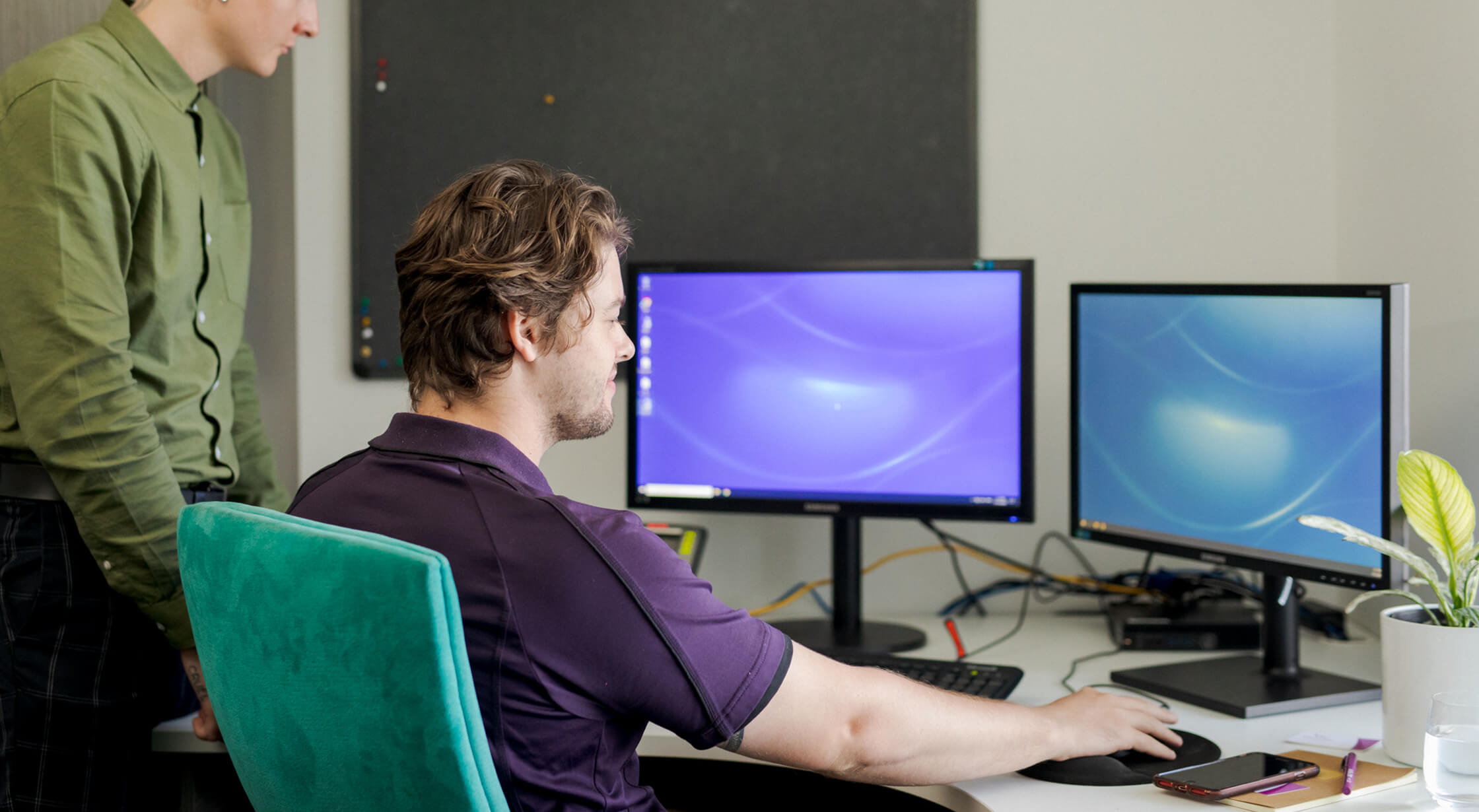 Two men look over at a set of desktop monitors. The man on the left is wearing a green shirt and standing. The man on the right is wearing a blue shirt and is seated behind the computer.
