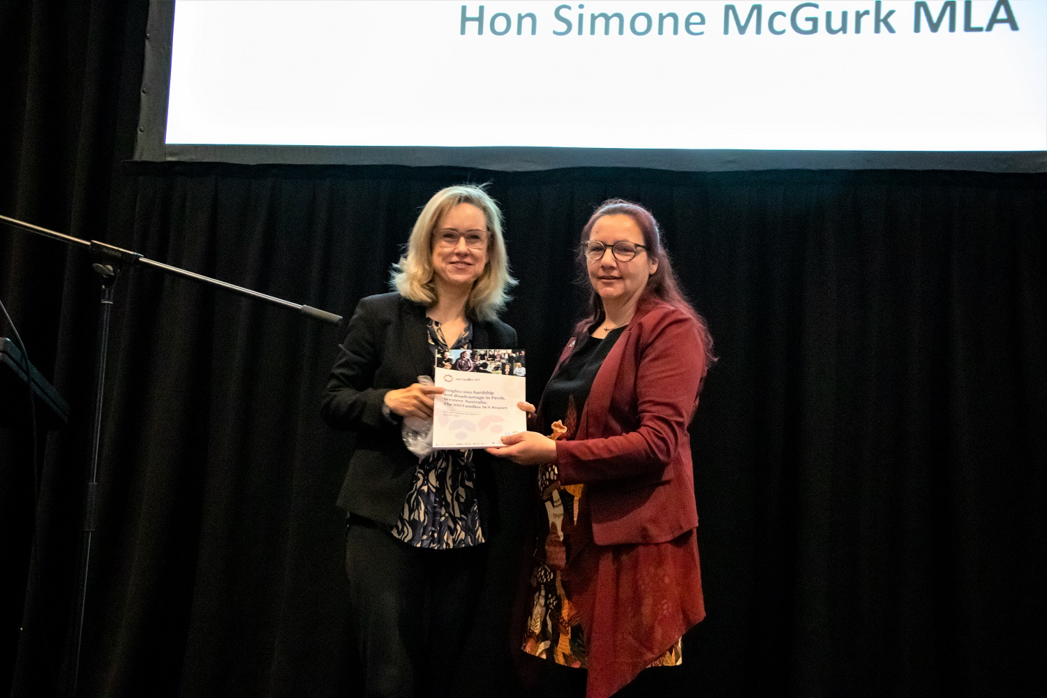 Minister Simone McGurk accepting 100 Families Report from Renna Gayde