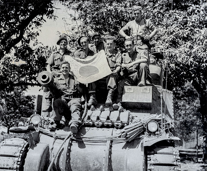 Historic photograph of soldiers sitting on a tank.