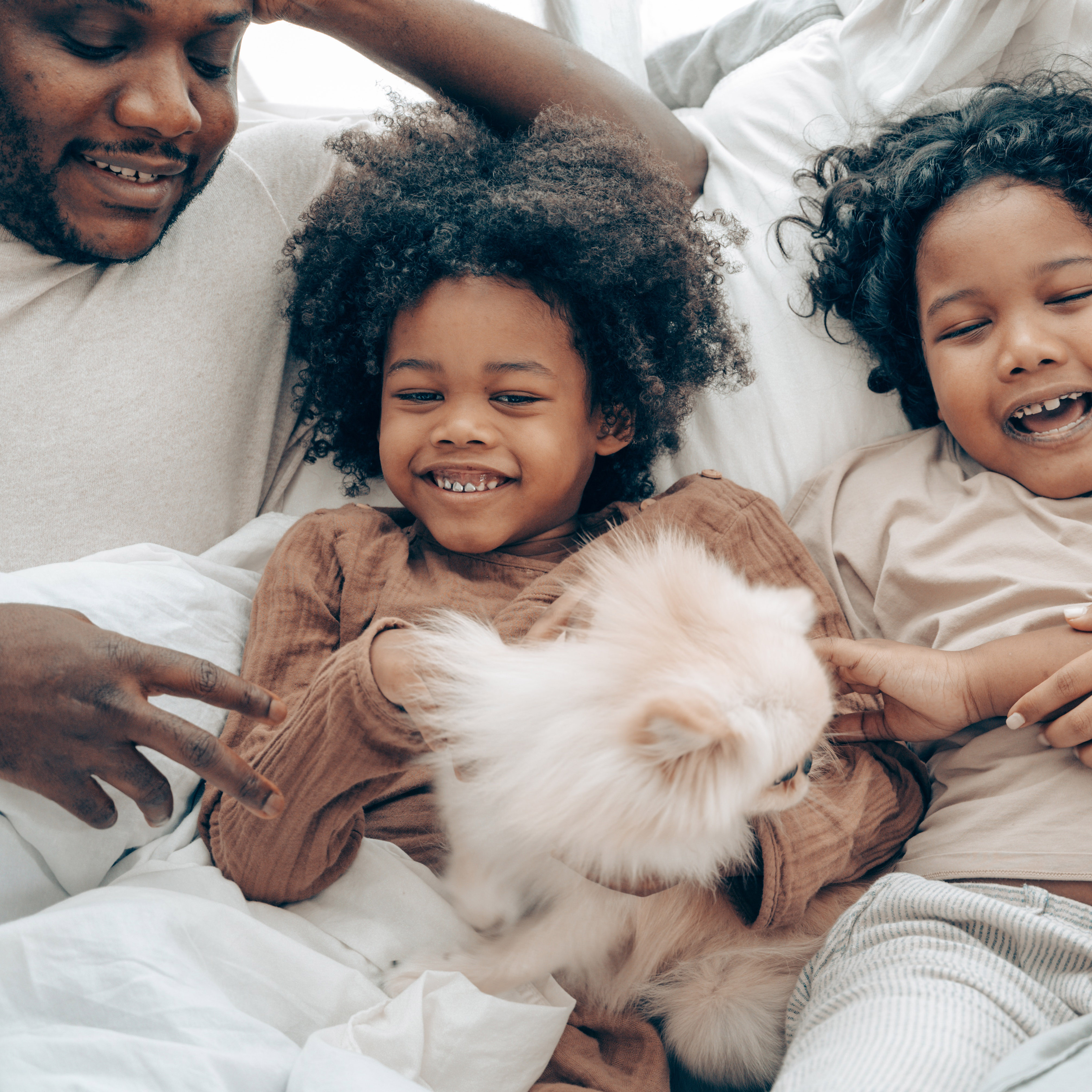 family laying down with their dog laughing