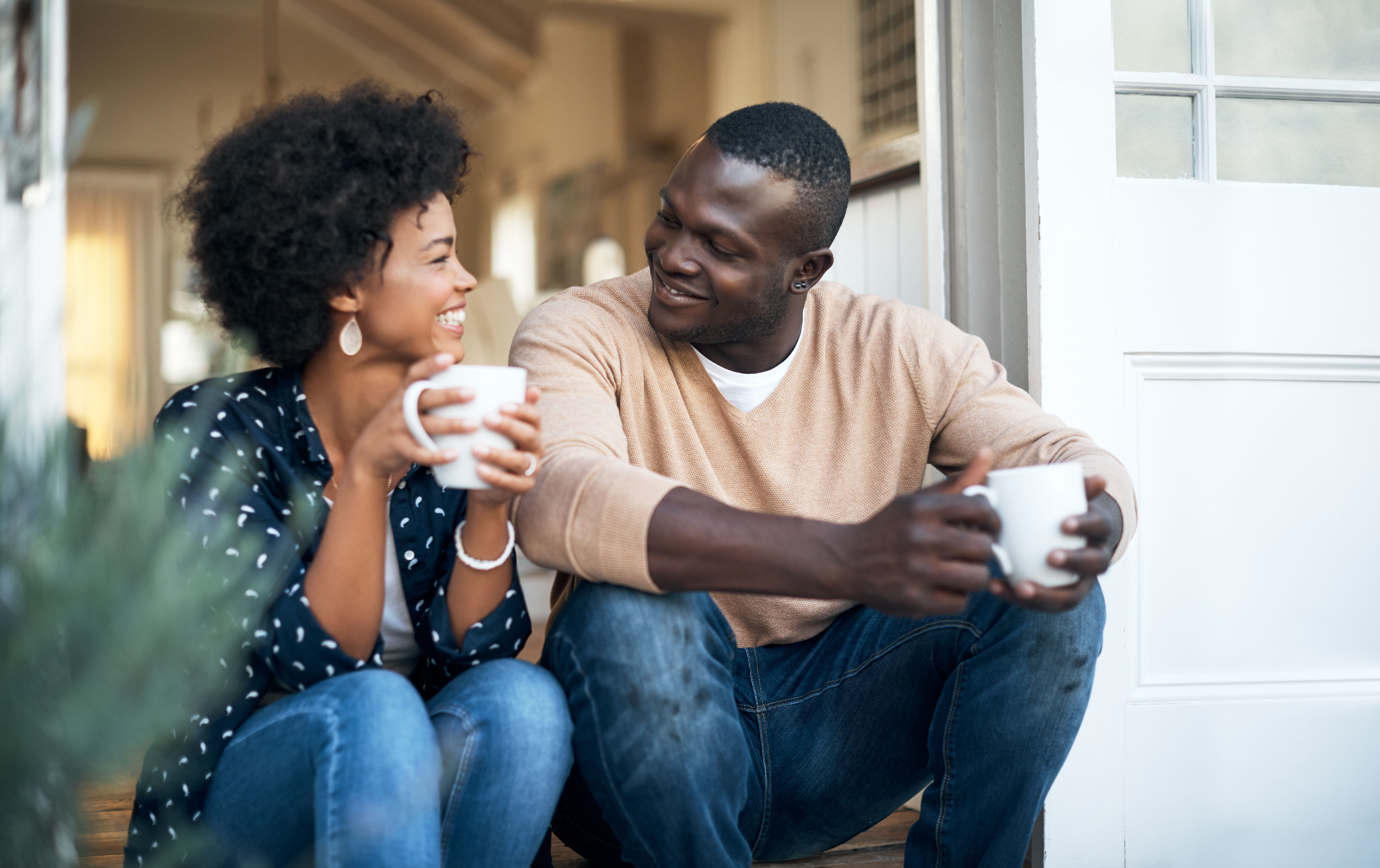 two people sitting outside talking and drinking coffee