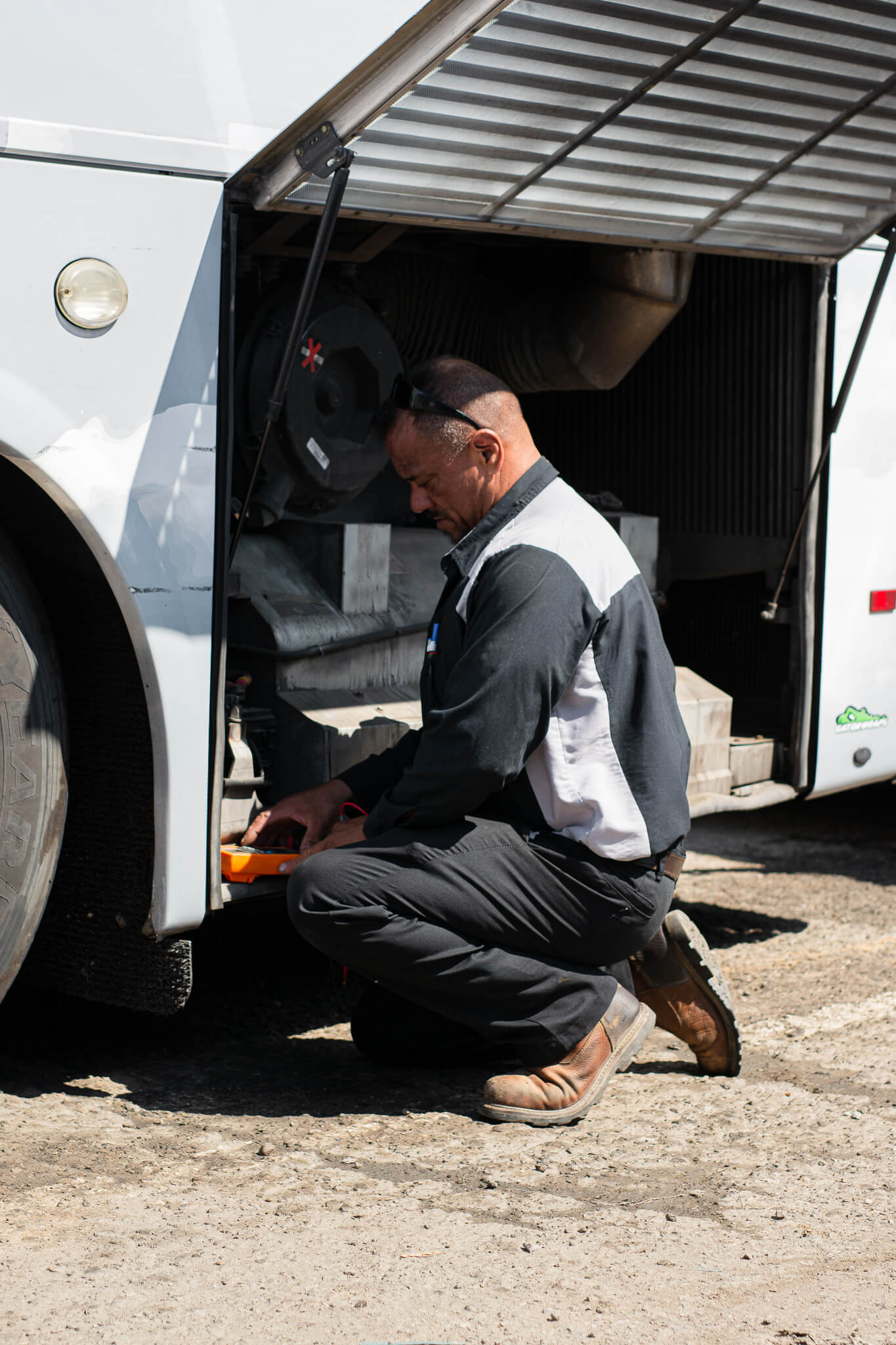 An image of a Pegasus Transit mechanic doing a diagnosis test on one of their charter buses.