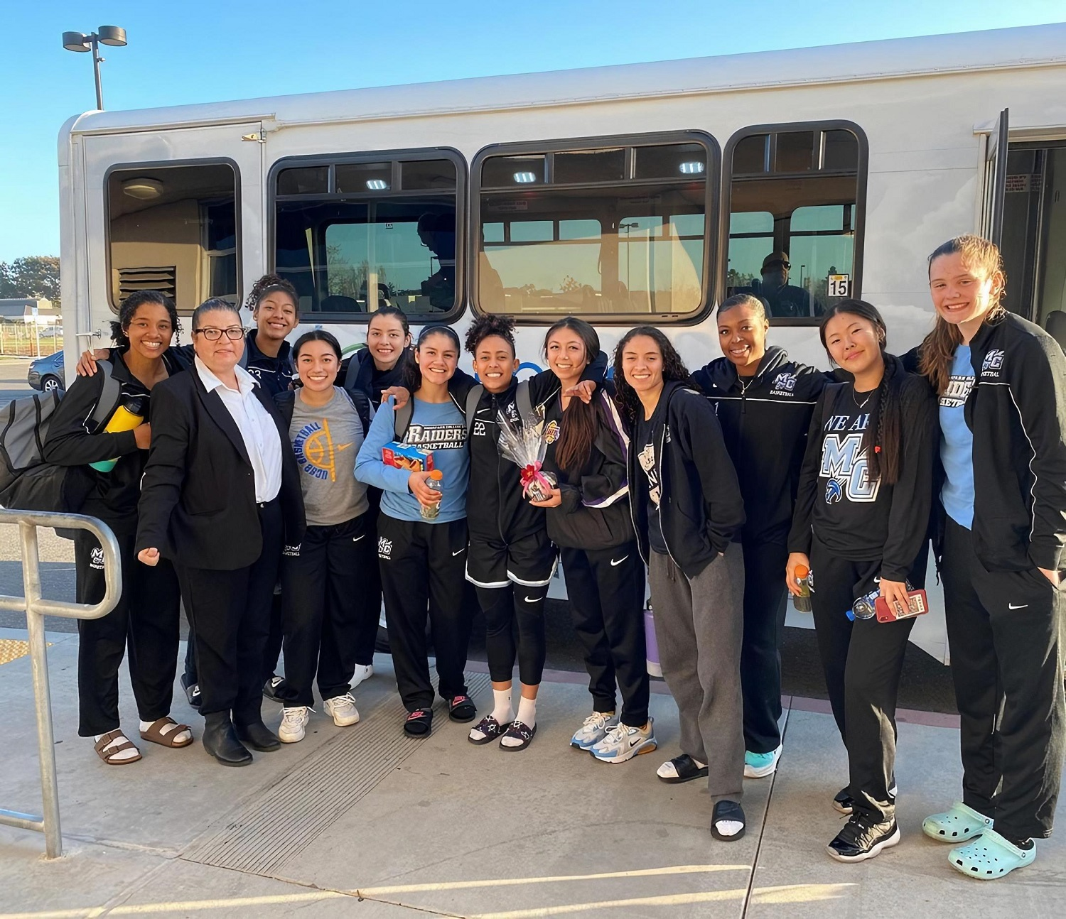 Image of highschool sports team being picked up by a Pegasus Transit shuttle bus.
