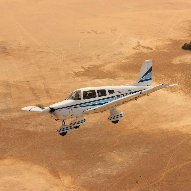 Fixed wing plane flying over desert landscape