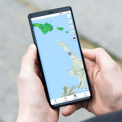 man holding android phone with weather maps displayed on the screen