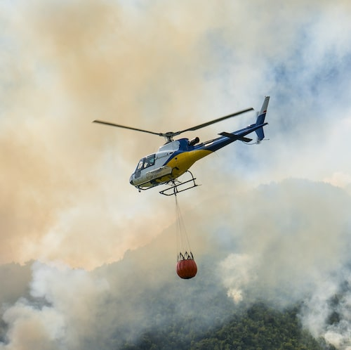 helicopter with bambi bucket flying over bush fires