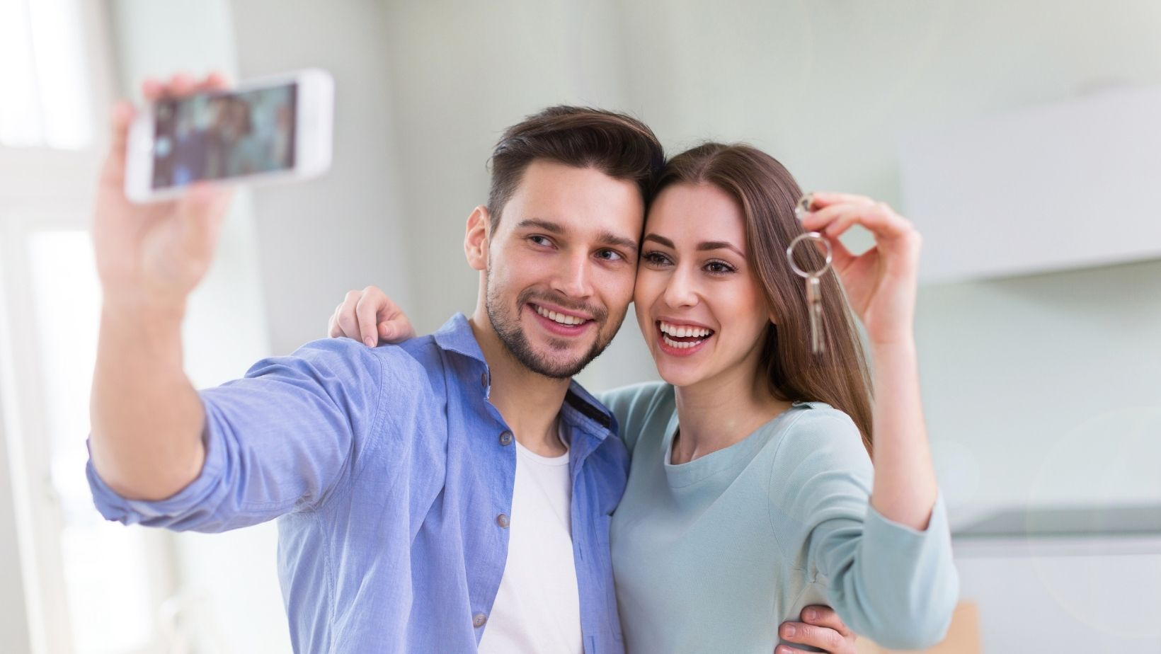 couple taking selfie with keys to new home