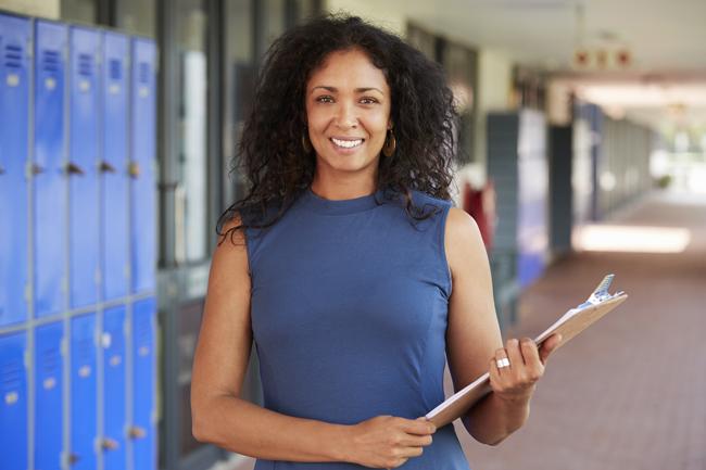 teacher in a hallway holding a clipboard