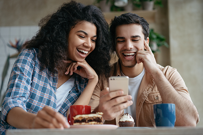 couple laughing looking at phone