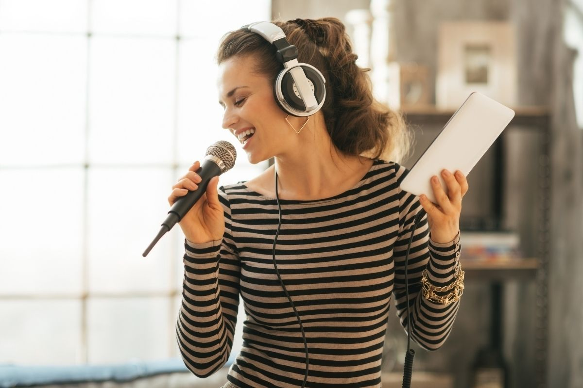 woman singing into microphone holding phone