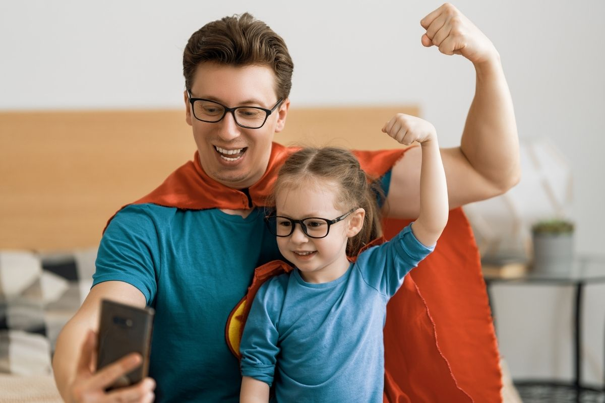 father and daughter in superhero costumes