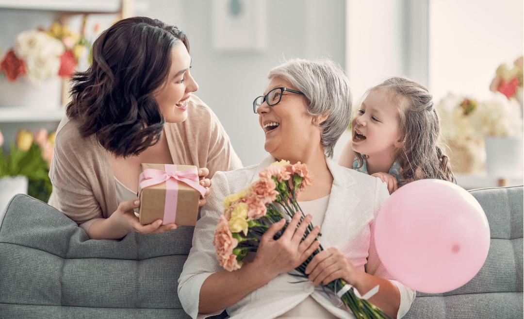 A grandma receives gift from her daughter and granddaughter.