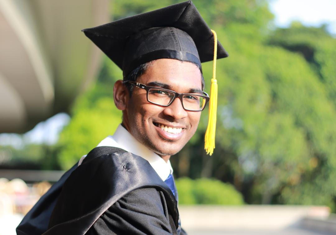 A young man in graduation hat and gown looks at camera, smiling.