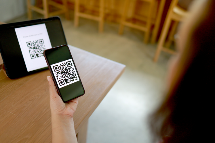 image showing lady customer scanning qr code on the table using her mobile phone