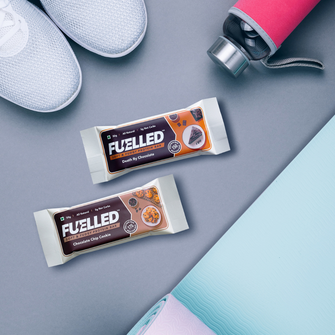 Fuelled Protein Bars Kept With Yoga Mat, Sport Shoes, and Water Bottle