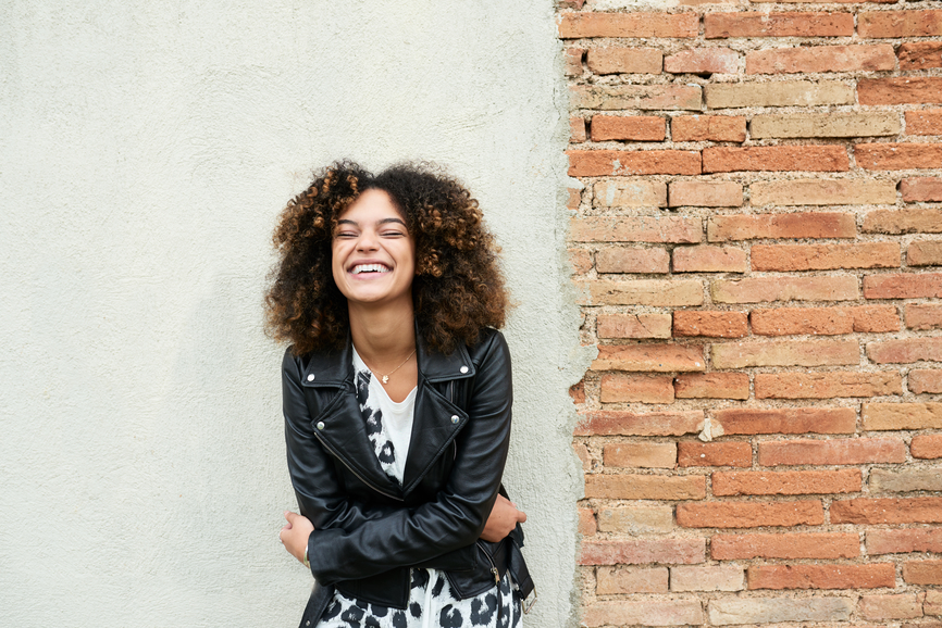 Woman sitting against a wall, laughing